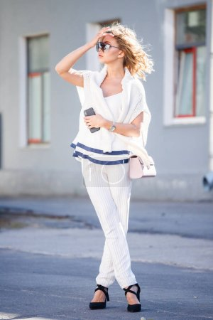 Outdoor portrait of beauty blond model wearing stylish white clothes and sunglasses. Young woman standing on street with smartphone in hands at daytime.