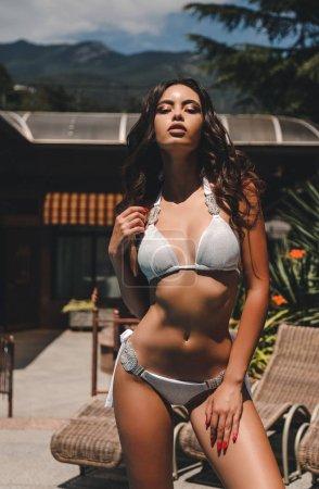 fashion outdoor photo of beautiful woman with dark hair in elegant bikini relaxing near swimming pool in villa