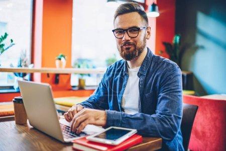 成功的胡须设计师在上网本做自由职业者时对着镜头微笑的半幅肖像。快乐商人键盘上的笔记本电脑键盘检查数据库通过无线网络