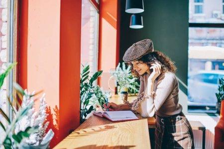 时尚微笑的女性作家在时髦的外观创造新的篇章站在舒适的自助餐厅, 积极的时髦女孩使用笔记本电脑在大学校园免费时间的课程工作
