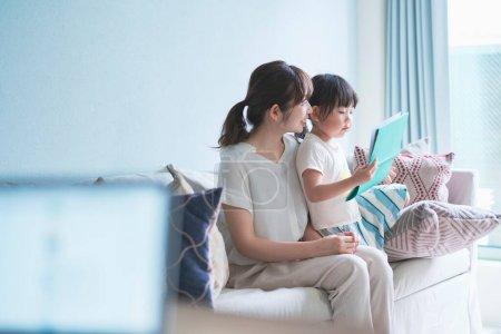 母亲和女儿坐在沙发上看画册_高清图片_邑石网