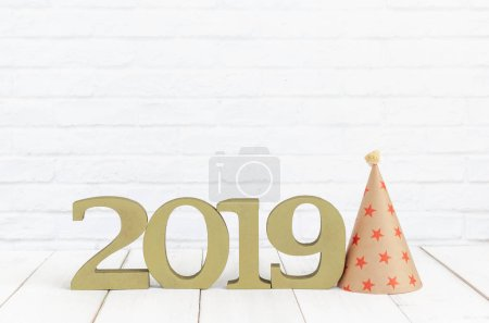 2019 new year and party hat on white wood table over white background with copy space
