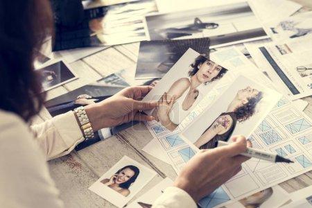 cropped shot of female magazine editor selecting models