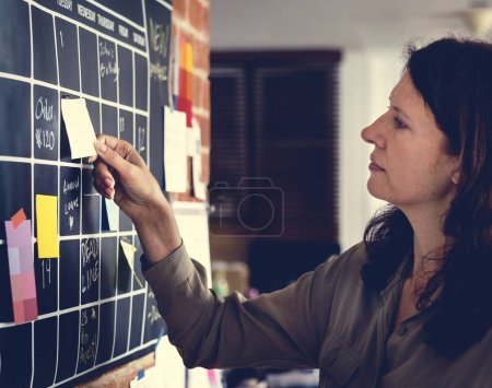 close-up shot of woman pulling sticky note on to do board at office