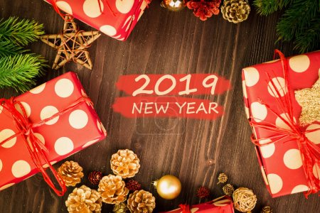 Christmas and New Year's Day festive decoration, red and golden balls, fir cones, branches and wooden stars with presents wrapped in red paper with golden circles on brown wood background with text 2019 New Year on red. Flat lay. View from above.