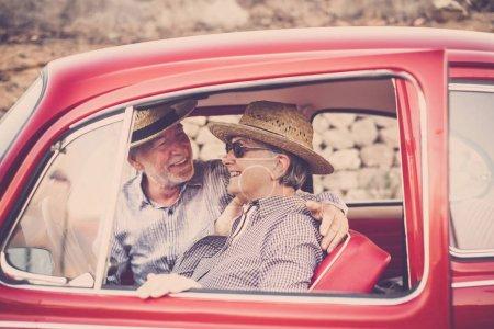为两个年长的男人和女人开一辆旧红车, 她微笑着看着你。都戴着帽子。另类旅游理念