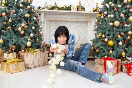 穿着格子衬衫和牛仔裤的漂亮女孩坐在打扮的圣诞树的背景上,手里拿着白色花环,有选择性的焦点_高清图片_邑石网