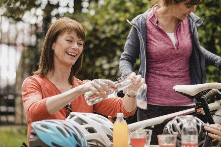 小群成熟的女性骑自行车的人坐在咖啡馆的外面休息区。泰伊正在享受一些茶点, 因为他们休息了一下