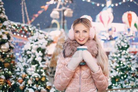 美丽快乐的女人举行咖啡杯白色手套粉红色冬季耳罩雪新年树和圣诞博览会景点的肖像_高清图片_邑石网