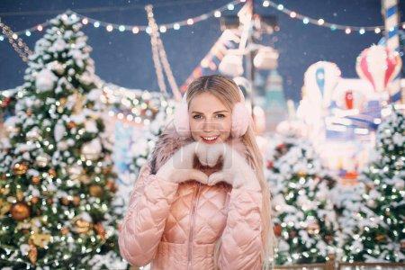 美丽的快乐的女人拿着心形状的手特写镜头白色的手套粉红色冬季耳罩雪新年树和圣诞博览会和情人节概念._高清图片_邑石网