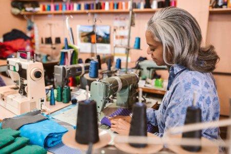 成熟的女裁缝坐在缝纫机上缝制一件五颜六色的布料, 同时独自在她的服装车间工作。