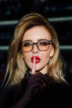 嘘.戴眼镜的女人要求用手指在红唇上保持沉默或保密。嘘手势