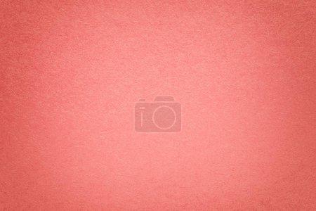 纹理的老式深粉红色的纸背景与晕影。密集的光的结构上升牛皮纸纸板与框架。毛毡渐变背景特写镜头