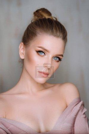 工作室肖像迷人的年轻金发女郎与蓝色的眼睛摆在背景
