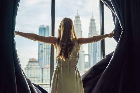 Young woman opens the window curtains and looks at the skyscrapers in the big city.